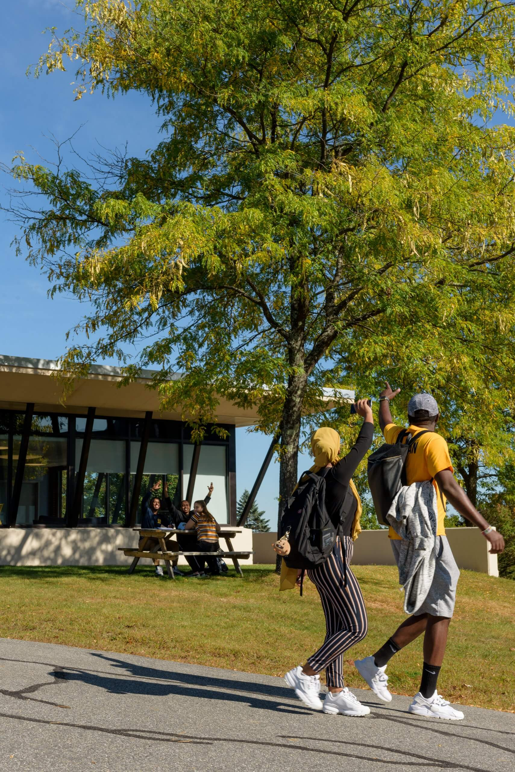 Two students on the USM campus waving to other students